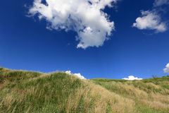 Hill under blue sky with clouds Royalty Free Stock Photo