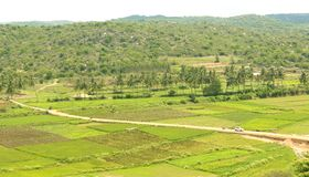 A hill view of agricultural fields with small village road. A hill view of an indian agricultural fields with small village road in the hosur, tamilnadu stock images