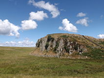The Hill. The view of a cliff face, also in shot is a small section of Hadrian's wall Stock Images