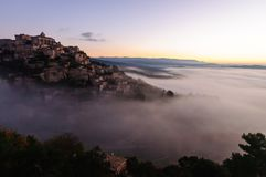 Hill village rising out of the clouds. / mise / Fog Village in the Provence / luberon Beautiful hill villages Gordes / France royalty free stock photos