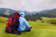 Hill walker is sitting in the middle of mountain wilderness. royalty free stock images