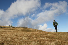 Hill walkers. Hill walkers enjoying the great outdoors on a grassy mountainside  with blue sky and cloud Royalty Free Stock Image