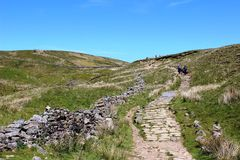 Hill walkers on constructed footpath on hillside Stock Image