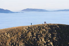 Hill Walking, English Lake District. Hill walkers on Riase enjoy the view across across a temperature inversion that blankets the dales and valleys below. In the Royalty Free Stock Photos