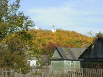 Hill with yellow trees in Russian village. The sight to summer cottages and hill in autumm Stock Photos