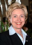 Hillary Clinton. With big smile, orchids in background royalty free stock photo
