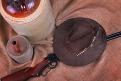 Hillbilly still life decor. A hillbilly still life decor with a rifle, a worn sloppy hat and moonshine jugs on burlap royalty free stock photography