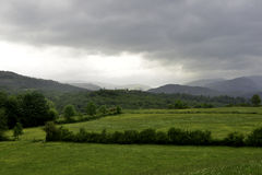 Hills across fields in the lake district Royalty Free Stock Image
