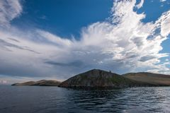 Hills on the background of the cool sky in the clouds on Lake Baikal. View from the water. On the water ripples stock photos