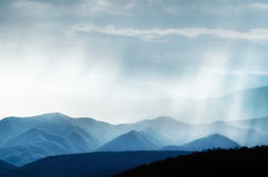 Hills with foggy, rainy and smoky ranges highlighted with sunlight Royalty Free Stock Photography