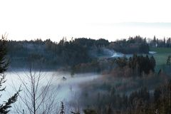 Hills and forest and a farmhouse just above the fog stock photo