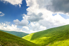 Hills with green grass and blue sky with white puffy clouds.  Royalty Free Stock Image