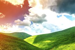 Hills with green grass and blue sky with white puffy clouds Stock Photo