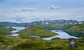 Hills, islands and lake water nordic landscape. Hills, islands and lake water nordic landscape with snow on the mountains. Norway Royalty Free Stock Images