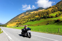 Among the hills motorcyclist rides Stock Photography