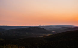 Hills receding into hazy distance under orange sky Royalty Free Stock Photos