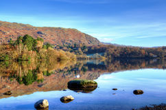 Hills reflected in Grasmere. On a sunny autumn day in the English Lake District Royalty Free Stock Photo