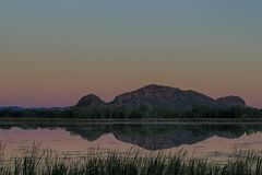 Hills reflected at sunset. The sun sets beyond hills at the edge of a lake in Northern Australia Royalty Free Stock Image