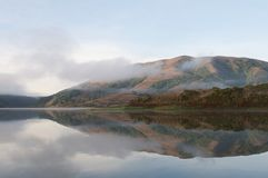 Hills reflected in surface of lake foggy morning Royalty Free Stock Photo
