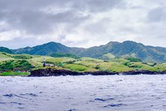 Hills of Sabtang Island with Lighthouse fronting the shore at, Batanes, Philippines.  royalty free stock photography
