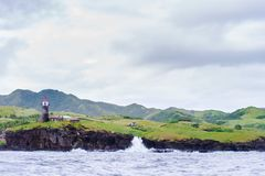 Hills of Sabtang Island with Lighthouse fronting the shore at, Batanes, Philippines.  royalty free stock photos