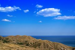 Hills and sea. Hills, sea and blue sky with clouds Royalty Free Stock Images