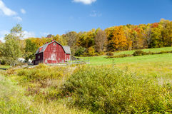 Hillside Barn. A large red barn at the bottom of a hill surrounded by a fence Stock Image