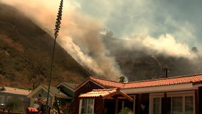 Hillside fire threatens a residential community stock video footage