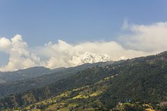 Hillside with green forest, fields and houses against the backdrop of the snowy mountain of Annapurna with white clouds and blue. A hillside with green forest stock images