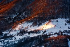 Hillside in red light on winter sunrise. Beautiful nature scenery in mountains Royalty Free Stock Photo