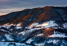 Hillside in red light on winter sunrise. Beautiful nature scenery in mountains Royalty Free Stock Image