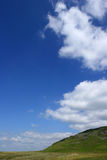 The Hillside and the Sky. Hillside adjoining a plain with a blue sky full of puffy white clouds. Set in the Brecon Beacons National Park, Wales, United Kingdom royalty free stock photo
