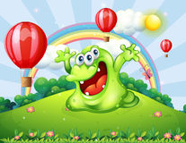 A hilltop with floating balloons and a green monster Stock Image