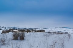 Hilltop full of snow empty sheepfold stock image