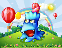 A hilltop with a happy blue monster holding a yellow balloon Stock Photography