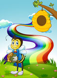 A hilltop with a rainbow and a bee near the beehive Royalty Free Stock Images