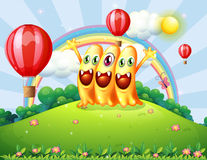A hilltop with three happy monsters watching the floating balloo Royalty Free Stock Images