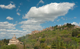 Hilltop town, Tuscany. WS - A traditional hilltop town - Montepulciano, Tuscany, Italy. LoF: The white marble church at the foot of the hill. Surrounding green Royalty Free Stock Photos