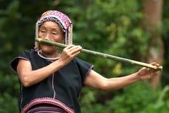 Hilltribe de Khmu que toca la flauta con la nariz. Fotografía de archivo