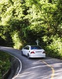 Hilly asphalt road with white car Stock Photos