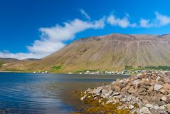 Hilly coastline on sunny blue sky in isafjordur, iceland. Mountain landscape seen from sea. Summer vacation on. Scandinavian island. Discover wild nature Royalty Free Stock Photos