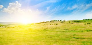Hilly green fields and sunrise on a blue sky. Wide photo. Stock Photos