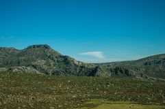 Hilly landscape covered by green fields and rocks. Countryside hilly landscape covered by green fields with bushes and rocks, in a sunny day at the Serra da royalty free stock images