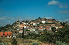 Hilly landscape with houses of a small village on top. Hilly landscape covered by trees and rocks in a sunny day, with houses of the small Sortelha village on stock photos