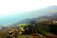Hilly landscape with houses partly covered by fog royalty free stock image