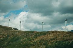 Hilly landscape and several wind generators of electric power. Hilly landscape covered by rocks and several wind generators of electric power, on cloudy day at royalty free stock photo