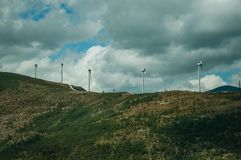 Hilly landscape and several wind generators of electric power. Hilly landscape covered by rocks and several wind generators of electric power, on cloudy day at royalty free stock images