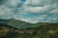 Hilly landscape and several wind generators of electric power. Hilly landscape covered by rocks and several wind generators of electric power, on cloudy day at stock image