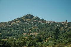 Hilly landscape with the small Monsanto village on top. Hilly landscape covered by trees and rocks in a sunny day, with the small Monsanto village on top of it stock image
