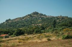 Hilly landscape with the small Monsanto village on top. Hilly landscape covered by trees and rocks in a sunny day, with the small Monsanto village on top of it stock photography